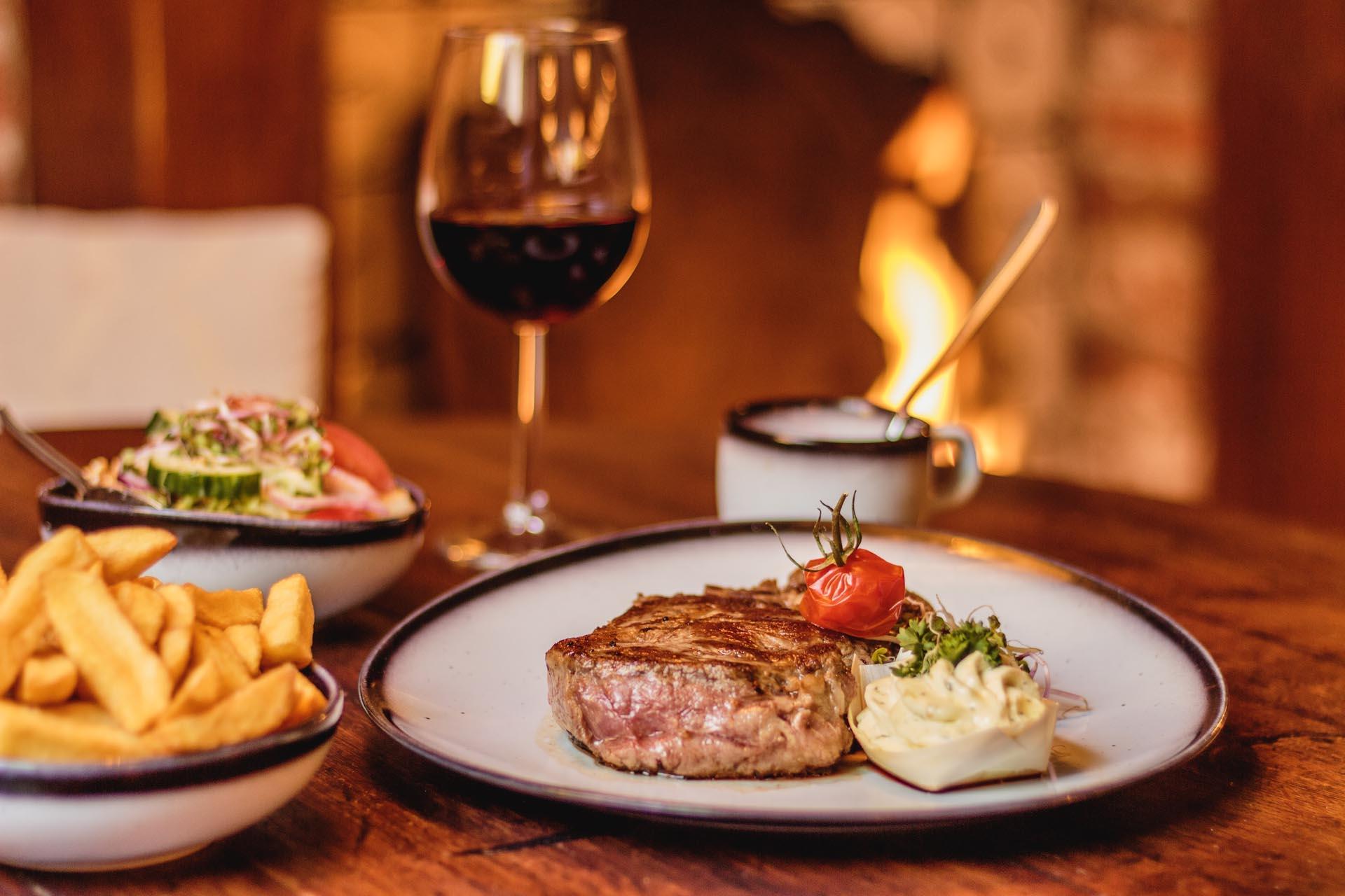 Volledig diner met een malse steak, verse frites, salade en rode wijn bij restaurant de klimop ameland